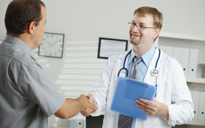 Medical office - middle-aged male doctor greeting patient, shaking hands.